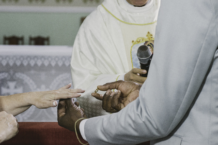 Momento religioso del intercambio de alianzas durante el matrimonio en la iglesia católica.