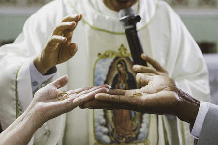 Religious moment of the exchange of alliances during the marriage in the catholic church.