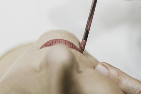 Donna che passa rossetto rosso nel salone di bellezza. Archivio Fotografico