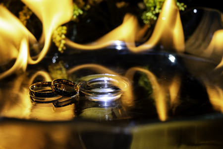Gold ring on glass with fire in the background.