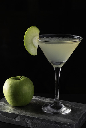 Apple Martini cocktail is on the bar. Space for text. Photo for the menu.