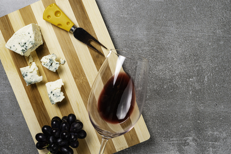Striped board with cheese and glass with wine on concrete background. Copy Space.