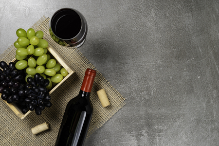 Wooden box with grapes bowl with wine on concrete background. Copy space. Stockfoto