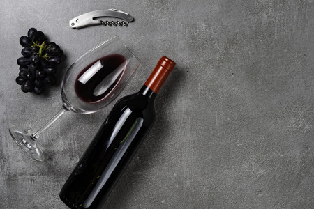 Glass with wine, bottle, opener and grapes on background of congreto. Copy Space.