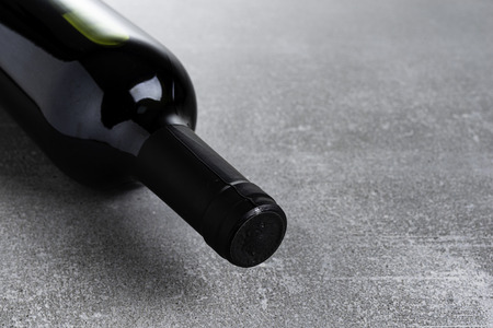Bottle of wine on gray concrete.