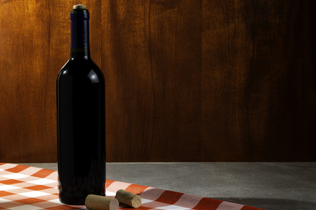 Bottle of red wine in wine cellar for tasting. Red wood background. Wine tradition and culture concept. Foto de archivo