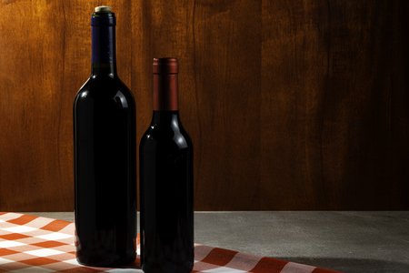 Bottle of red wine in wine cellar for tasting. Red wood background. Wine tradition and culture concept. Zdjęcie Seryjne