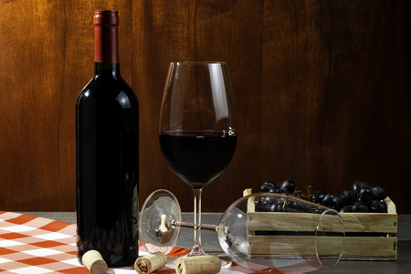 Bottle of red wine in wine cellar for tasting. Red wooden background with wooden box with grapes. Wine tradition and culture concept.