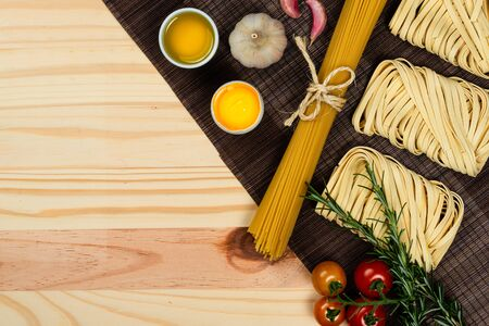Composition with different types of pasta on pine wood background. Space for text. 免版税图像