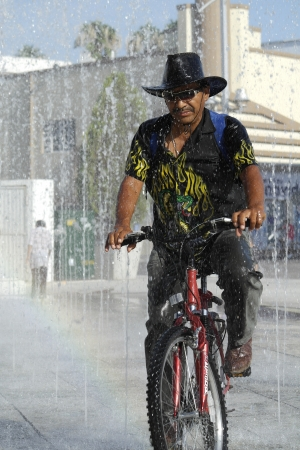 Man in bicycle refreshing in fountain Stok Fotoğraf