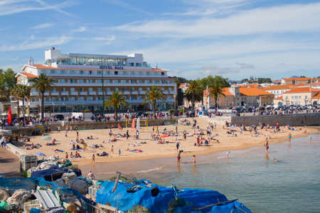 CASCAIS, PORTUGAL - APRIL 14, 2017: People swimming on Cascais main beach on Holy Week break with hotel background