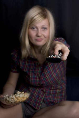 Young woman eating popcorn and watching TV at home photo