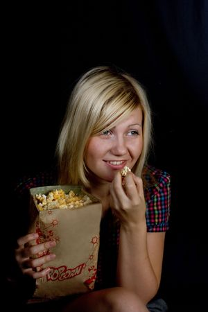 The girl smiles and eats popcorn photo