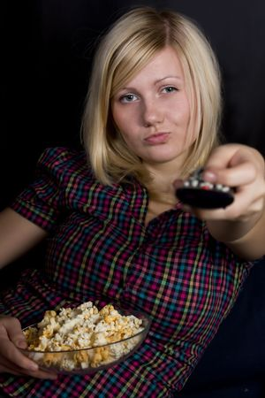girl eating popcorn and watches TV photo