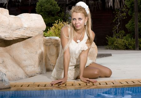 beautiful girl in a white dress sits on the brink of pool photo