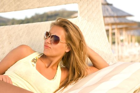 beautiful girl in dark glasses lies in a wicker chair photo