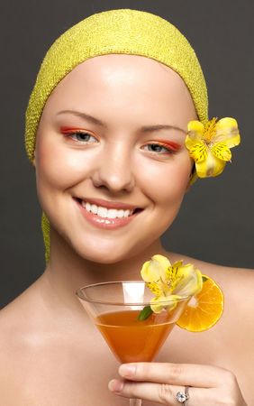 Portrait of the beautiful smiling girl with a cocktail from oranges photo