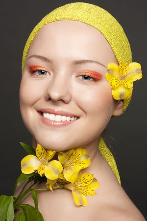beautiful smiling girl with a yellow flower and a yellow scarf on a grey background photo