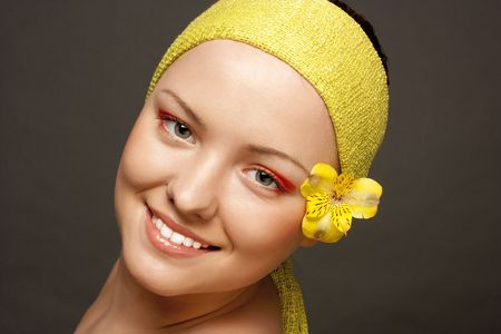 beautiful smiling girl with a yellow flower Stock Photo - 6147066