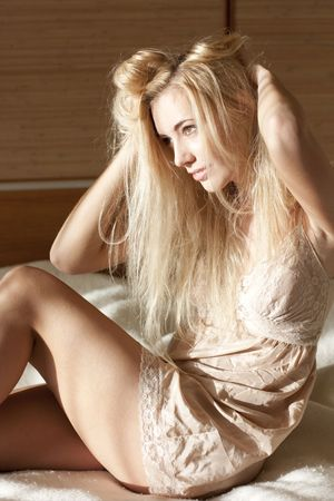 Portrait of smiling blonde woman on the bed photo