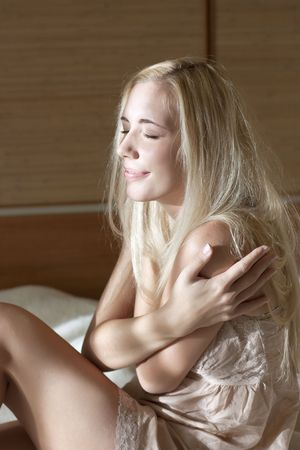 Portrait of smiling blonde woman on the bed Stock Photo - 6244764