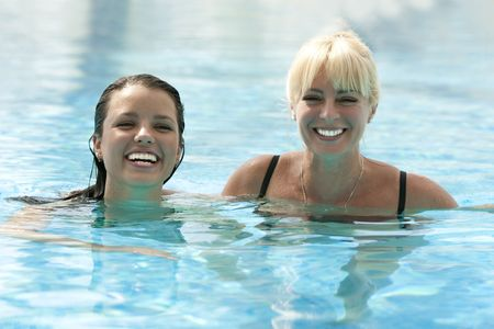 Portrait of two happy women in pool with blue water photo
