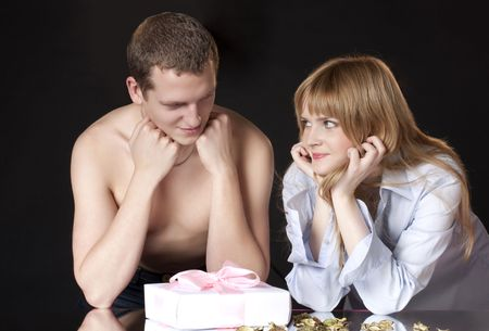 man and the woman with a gift on a black background  photo