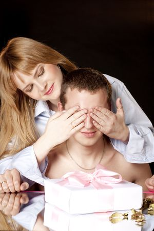 Happy woman covering her husbands eyes to surprise him with a gift photo