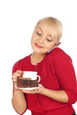 Smiling young blond woman holding a phone and cap of coffee. Isolated on a white background. photo