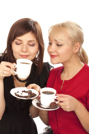 two girls drinking coffee over white background photo