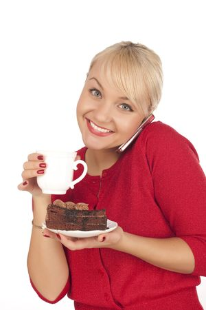 Smiling young blond woman holding a phone and cap of coffee. Isolated on a white background photo