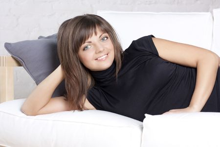 Portrait of the beautiful smiling girl on a white sofa photo
