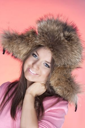 Portrait  of young girls in a fur cap on a pink background Stock Photo - 6473153