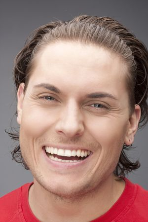 Portrait of the beautiful happy man in red on a grey background. �lose up photo