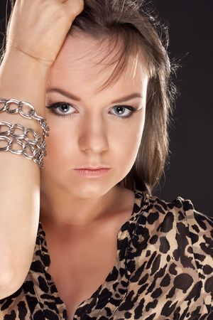Portrait of the beautiful young girl in a leopard dress. Close-up photo