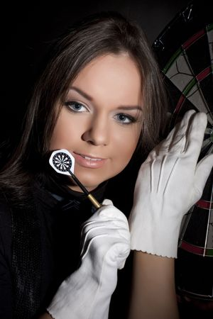 beautiful girl in white gloves holding dart on a black background. Close-ap photo