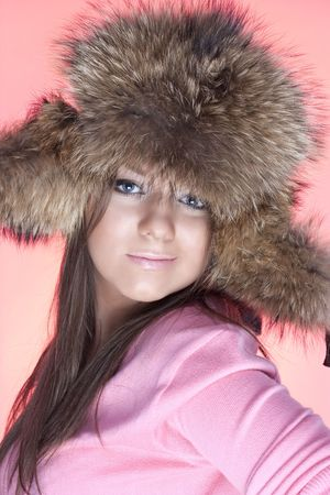Portrait  of young girls in a fur cap on a pink background photo