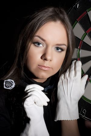 Beautiful girl in white gloves holding dart on a black background. Close-ap Stock Photo - 6504413