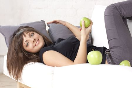 Portrait of the beautiful smiling girl with green apples on a white sofa photo
