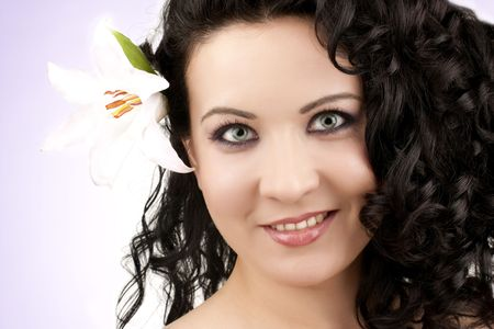 beautiful woman with a lily flower on a pink background photo