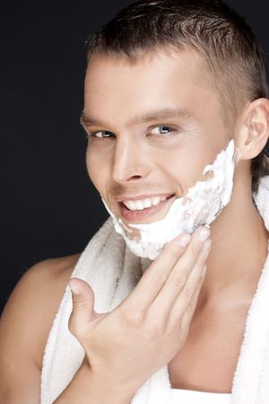 Portrait of  young handsome men shaving on a black background photo
