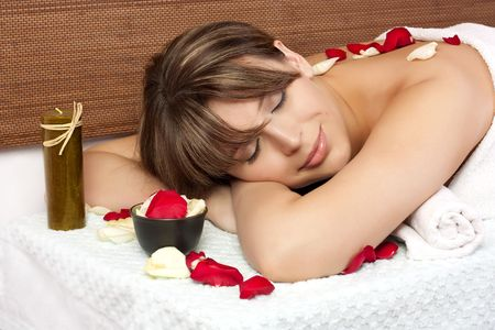 Beautiful woman on massage table with petal of rose photo