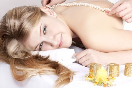 beautiful girl on procedure of massage by pearls  photo