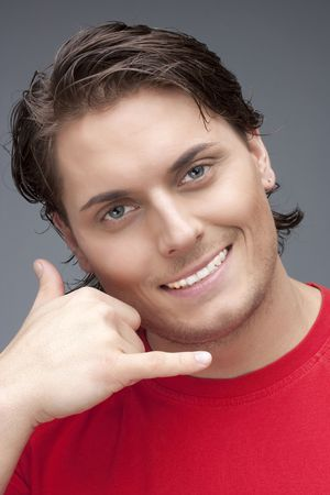 Young man using a call me gesture Stock Photo - 6768686
