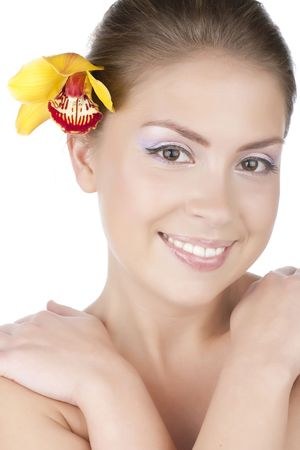 Portrait of a beautiful girl with a yellow orchid