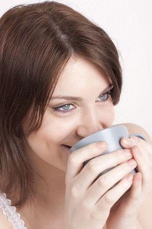 The beautiful young woman drinks morning coffee or tea photo