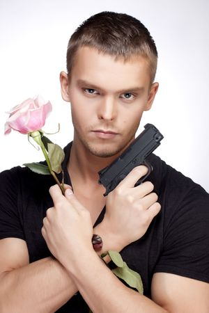 man holding gun: Young handsome man with pink rose and gun