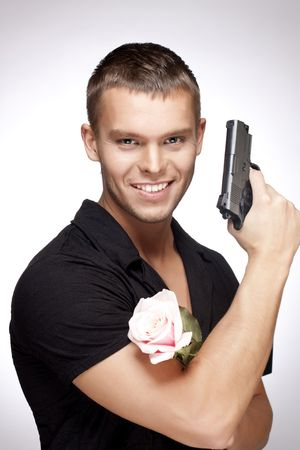 Young handsome man with pink rose and gun  photo