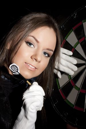 beautiful girl in white gloves holding dart on a black background. Close-ap Stock Photo - 6813251