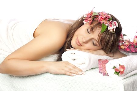 Beautiful woman on massage table with flower in hair photo